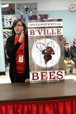 a  woman holds up a sign with a red bee on it