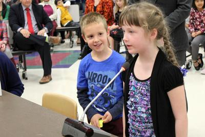 a young girl speaks into a microphone while a little boy looks on
