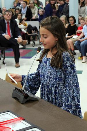 a young girl speaks into a microphone to read a note