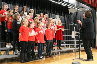 a chorus of young boys and girls dressed in red sing as their teacher directs them
