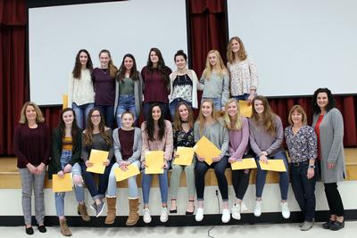 Female volleyball players sit and stand on a stage, holding certificates