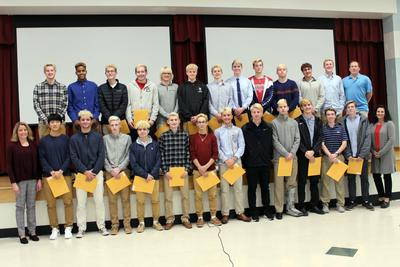 Twenty-eight boys soccer players stand in front of and on a stage holding certificates