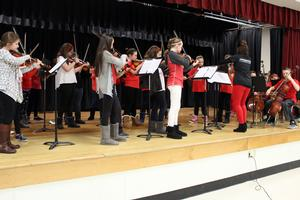 student orchestra members performing on a stage