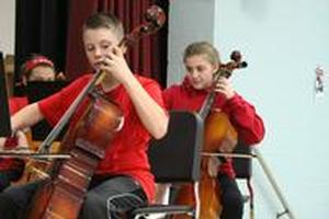 children playing the cello on a stage