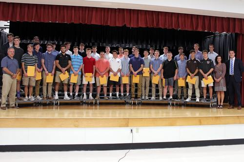 a group of 30 boys stand on a stage