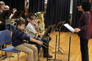 a teacher directs students playing brass instruments