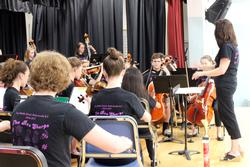 a group of students perform with cellos and violins